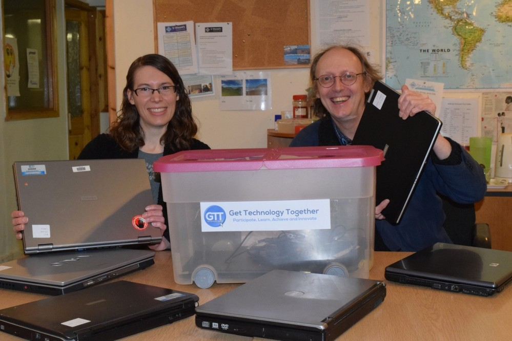 Picture shows laptop donations being given to GTT