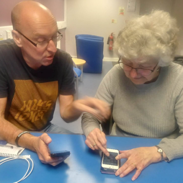 Volunteer helping an older lady with her smartphone